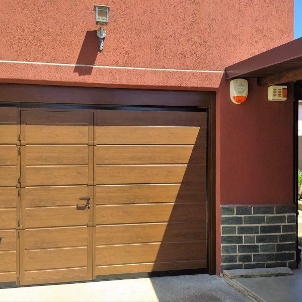Porta sezionale residenziale effetto legno ciliegio modello Urbino con porta pedonale inserita
